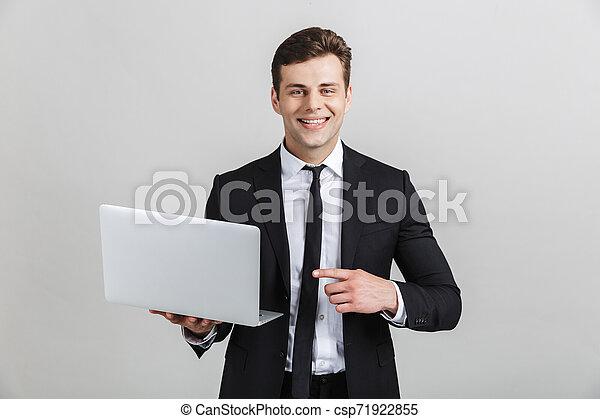 brunette, wijzende, beeld, terwijl, fototoestel, vinger, kostuum, zakenman, het glimlachen, formeel, draagbare computer, aantrekkelijk - csp71922855